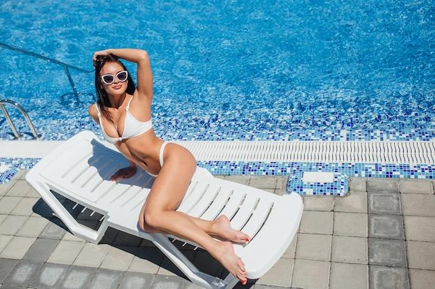 Junges schönes brünettes mädchen in einem weißen badeanzug in der sonnenbrille, die sich am pool sonnen