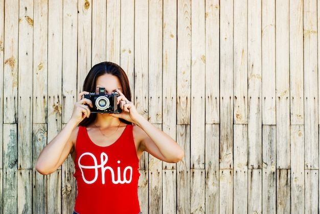 Junges schönes brunettemädchen in der roten hemd- und jeanshose, die mit einer kamera auf dem rustikalen hölzernen hintergrund aufwirft.