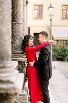 Junges schönes chinesisches paar in der liebe, die einander auf der alten stadtstraße umarmt