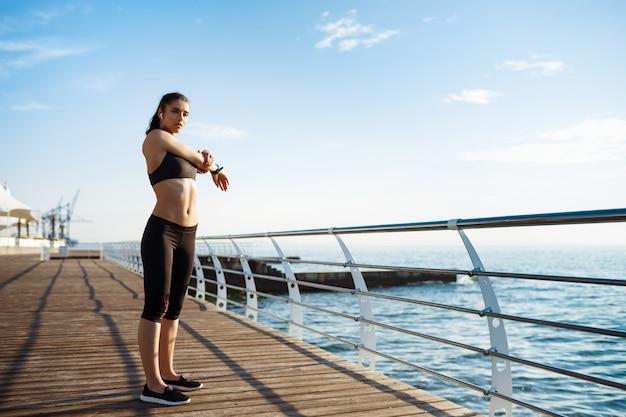 Junges schönes fitnessmädchen macht sportübungen mit seeküste an der wand