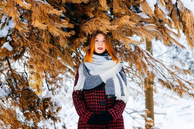 Junges schönes foxy mädchen mit dem roten haar im winter kleidet die aufstellung für kamera im schneebedeckten wald im freien