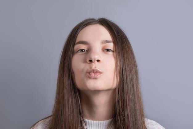 Junges schönes frauenporträt mit dunklem haar, das weißen pullover trägt
