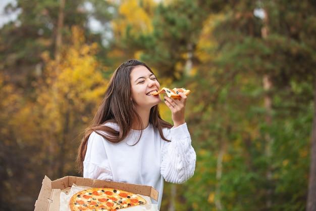 Junges schönes fröhliches mädchen, das pizza isst, während es den geschmack in der natur genießt