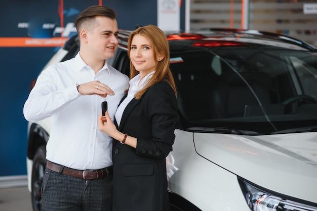 Junges schönes glückliches paar, das ein auto kauft. ehemann kauft auto für seine frau in einem salon. auto-shopping-konzept.
