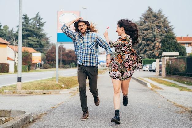 Junges schönes glückliches paar, das im freien läuft