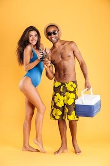 Junges schönes glückliches sommerpaar, das glasflaschen und kühltasche für picknick lokalisiert auf der orange wand hält