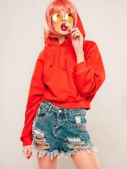 Junges schönes hipster böses mädchen im trendigen roten sommer roten kapuzenpulli und ohrring in ihrer nase. sexy sorglose frau, die im studio auf grauem hintergrund in perücke aufwirft. heißes modell leckt runde kandiszucker