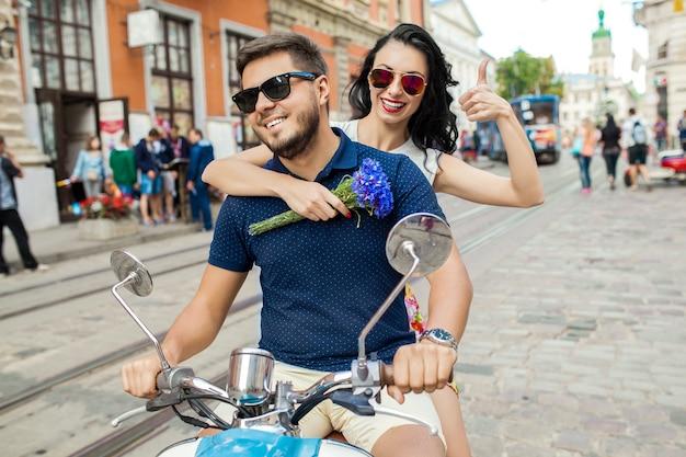 Junges schönes hipster-paar, das auf motorradstadtstraße reitet