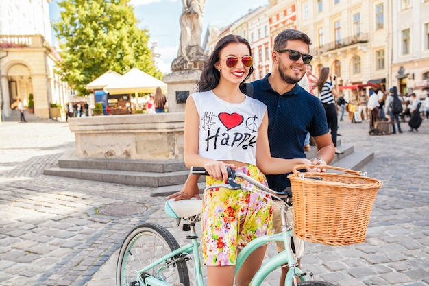 Junges schönes hipster-paar in der liebe, die mit fahrrad auf altstadtstraße geht