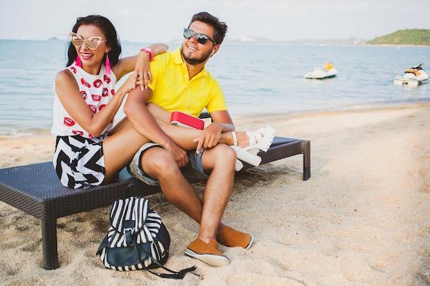 Junges schönes hipster-paar in der liebe sitzen am strand, musik hören, sonnenbrille, stilvolles outfit, sommerferien, spaß haben, lächeln, glücklich, bunt, positive emotionen
