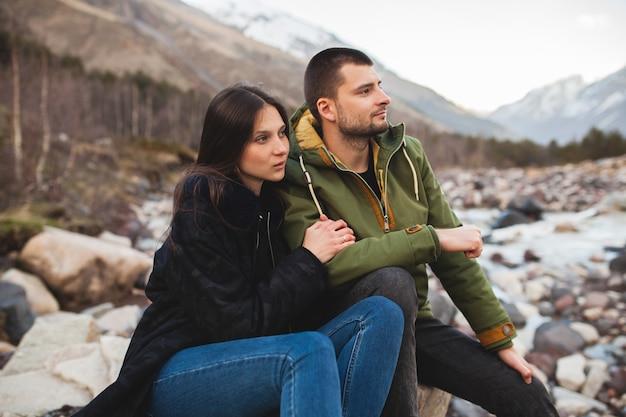 Junges schönes hipster-paar verliebt, am fluss sitzend, wilde natur, winterferien