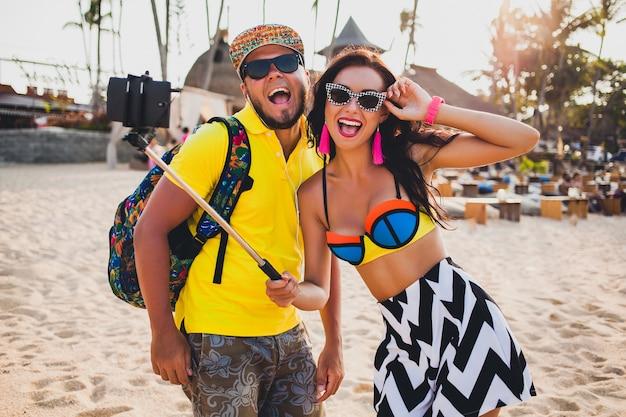 Junges schönes hipster-paar verliebt in tropischen strand, selfie-foto auf smartphone, sonnenbrille, stilvolles outfit, sommerferien, spaß haben, lächelnd, glücklich, bunt, positive emotion