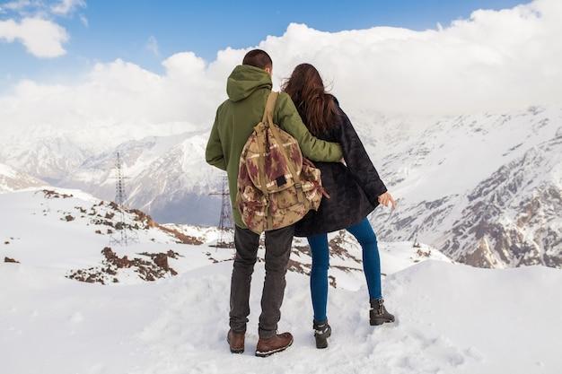 Junges schönes hipsterpaar, das in den bergen wandert, winterferienreisen, mann frau in liebesansicht von hinten