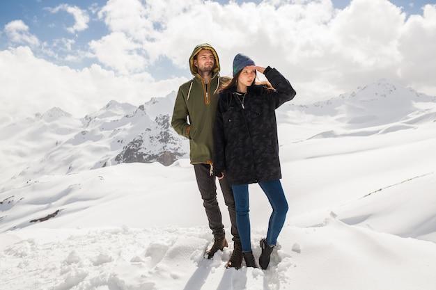 Junges schönes hipsterpaar, das in den bergen wandert, winterferienreisen, mannfrau in der liebe