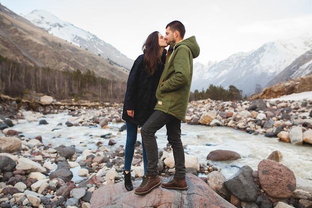 Junges schönes hipsterpaar verliebt, das durch den fluss, wilde natur, winterferien geht