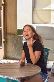 Junges schönes jugendlich mädchen, das kokosnussbonbons in der terrasse isst