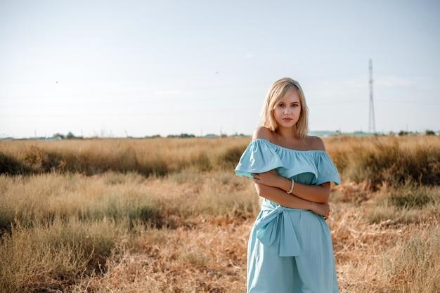 Junges schönes kaukasisches blondes mädchen im hellblauen kleid steht auf dem feld mit dem sonnenversengten gras