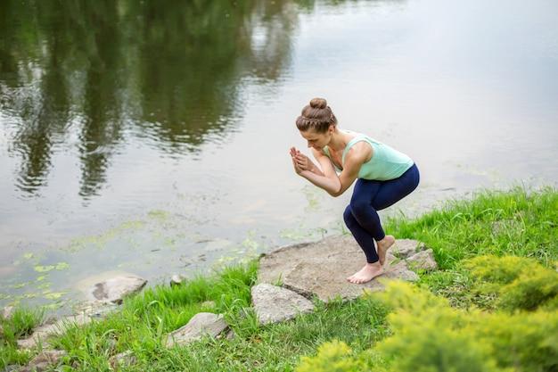 Junges schönes kaukasisches brunettemädchen, das yoga auf einem grünen rasen vor dem hintergrund des flusses tut