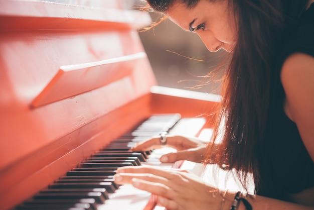 Junges schönes kaukasisches mädchen, das klavier spielt