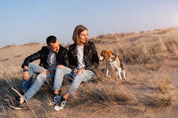 Junges schönes kaukasisches paar mit beagle-hund