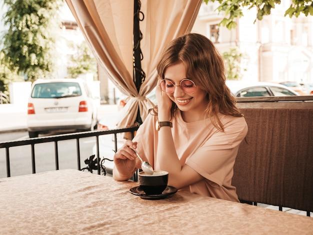 Junges schönes lächelndes hipster-mädchen in den trendigen sommerkleidern. sorglose frau, die im veranda-terrassencafé sitzt und kaffee trinkt. positives modell, das spaß und träume hat