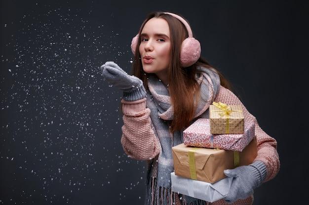Junges schönes lächelndes mädchen beim stricken des pullovers und der rosa flaumigen ohrenschützer, die geschenkboxen halten