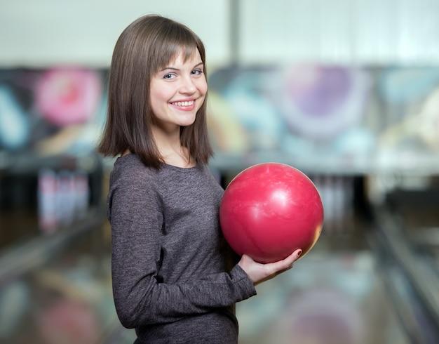Junges schönes lächelndes mädchen, das bowlingspiel spielt.