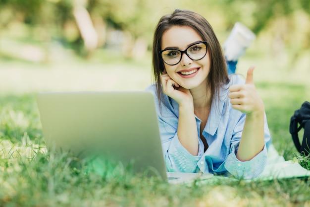 Junges schönes lächelndes modell unter verwendung des neuen laptops im stadtpark am sonnigen tag