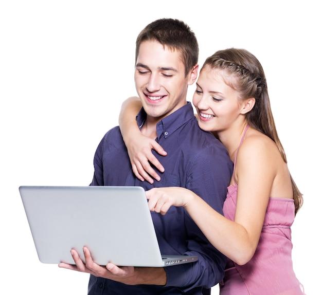 Junges schönes lächelndes paar, das laptop betrachtet - lokalisiert