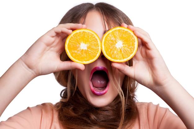 Junges schönes lustiges mädchen mit orangenscheibe und make-up und frisur, die kamera betrachten. studioaufnahme, isoliert auf weißem hintergrund. .