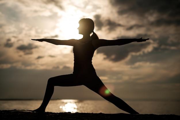 Junges schönes mädchen an der küste praktiziert yoga. sonnenuntergang silhouette.
