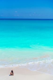 Junges schönes mädchen auf dem strand am draufsichthintergrund des flachen tropischen wassers