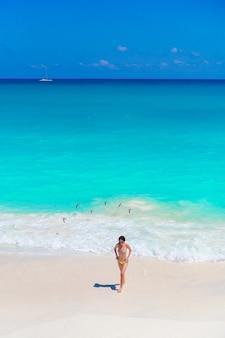 Junges schönes mädchen auf dem strand an der draufsicht des flachen tropischen wassers