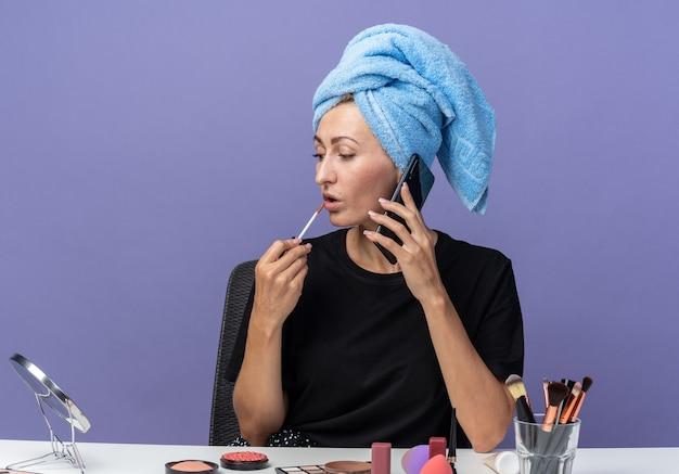 Junges schönes mädchen auf der suche nach seite sitzt am tisch mit make-up-werkzeugen, die haare im handtuch abwischen, spricht am telefon mit lipgloss isoliert auf blauer wand