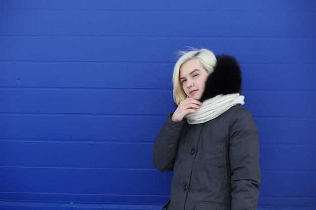 Junges schönes mädchen auf einem spaziergang im winter am blauen wandhintergrund