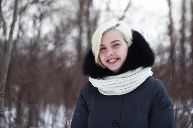 Junges schönes mädchen auf einem spaziergang in einem winterpark