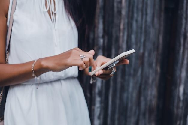 Junges schönes mädchen benutzt ein smartphone auf der straße und surft das internet