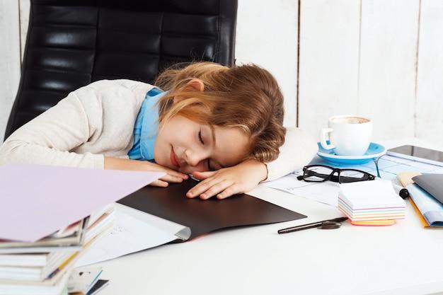 Junges schönes mädchen, das am arbeitsplatz im büro schläft.