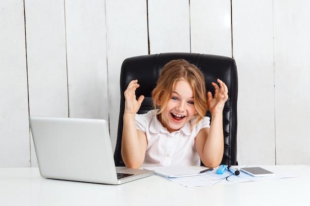Junges schönes mädchen, das am arbeitsplatz sitzt und im büro lacht.