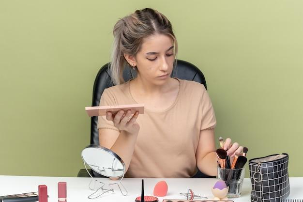 Junges schönes mädchen, das am tisch mit make-up-tools sitzt und pinsel mit lidschatten-palette auf olivgrünem hintergrund hält