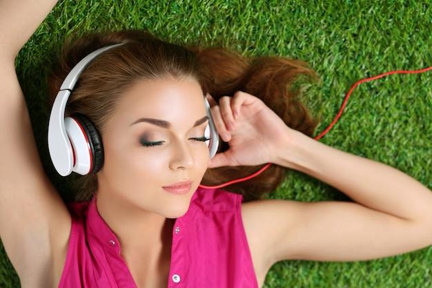 Junges schönes mädchen, das auf dem gras im park liegt, der musik hört. sommer- und freizeitkonzept. draufsicht.