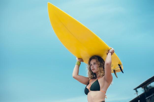 Junges schönes mädchen, das auf dem strand mit einem surfbrett, frauensurfer, meereswogen aufwirft