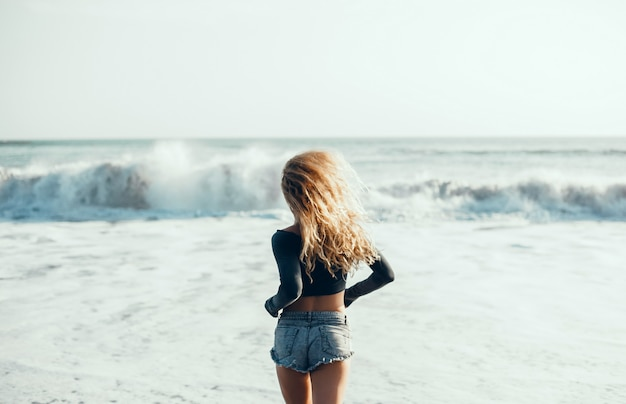 Junges schönes mädchen, das auf dem strand, ozean, wellen, heller sonne und gebräunter haut aufwirft