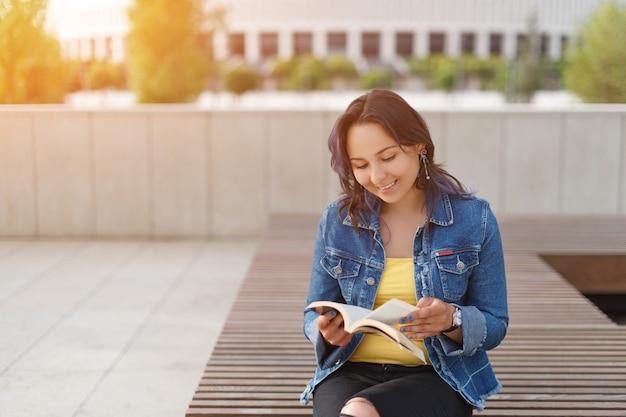 Junges schönes mädchen, das auf einer bank im park sitzt, ein buch und ein lächeln liest