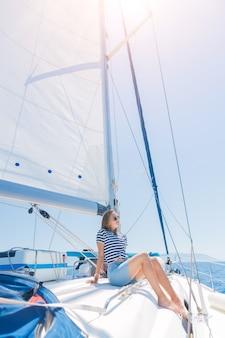 Junges schönes mädchen, das auf yacht in griechenland sich entspannt