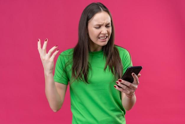 Junges schönes mädchen, das grünes t-shirt hält, das smartphone betrachtet, das bildschirm enttäuscht enttäuschtes gefühl irritiert steht über lokalisiertem rosa hintergrund