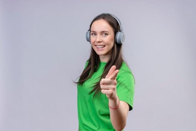 Junges schönes mädchen, das grünes t-shirt mit kopfhörern trägt, die positiv und glücklich lächeln, zeigen auf kamera, die über lokalisiertem weißem hintergrund steht