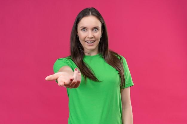 Junges schönes mädchen, das grünes t-shirt trägt, das kamera mit glücklichem gesicht macht, kommt hierher geste mit hand, die über lokalisiertem rosa hintergrund steht