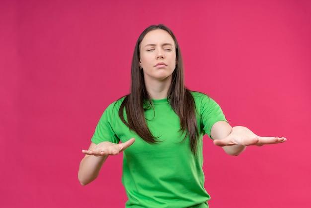 Junges schönes mädchen, das grünes t-shirt trägt, das mit geschlossenen augen geht, die ihre hände heraushalten, um straße zu finden, die über isoliertem rosa hintergrund steht