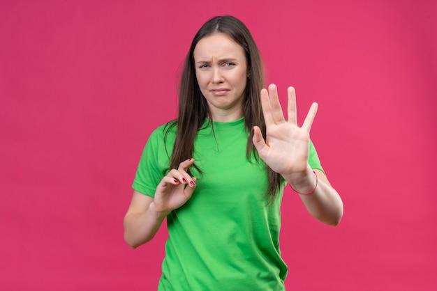 Junges schönes mädchen, das grünes t-shirt trägt, das verteidigungsgeste mit offenen händen mit angewidertem ausdruck auf gesicht hält, das hände hochhält und sagt, kommt nicht näher und steht über isoliertem rosa ba